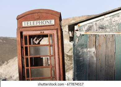 A derelict UK red telephone box stands abandoned and unloved next to a shabby looking building
