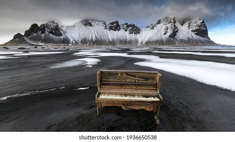 A derelict upright piano washed up on the black sand beach of the Stokksnes peninsula with the majestic, snow-capped Vestrahorn mountains in the background.  - Shutterstock ID 1936650538