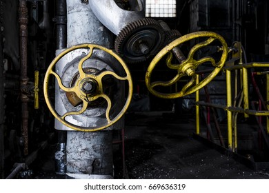 A derelict view of valves and wheels inside an abandoned power plant in New York.