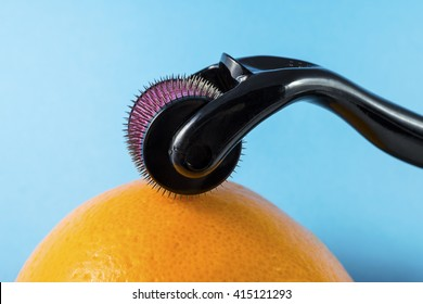 Derma roller for medical micro needling therapy with orange. Tool also known as: Derma roller, mesoroller, meso-roller, mesopen.