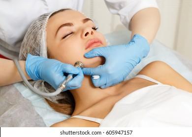 Dermabrasion cheekbones girl. Machine cosmetology. Spa. Facial Rejuvenation. Mechanical peeling skin.
