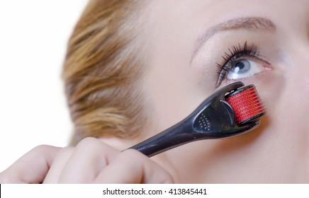 Dermaroller. Dermoroller.Medical cosmetic procedure. Microneedling. Beautician performs Dermaroller procedure