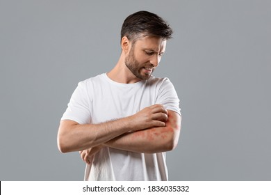 Dermatitis, eczema, allergy, psoriasis concept. Annoyed middle-aged man in white t-shirt scratching itch on his arm, grey studio background. Bearded man itching rash on his elbow, copy space