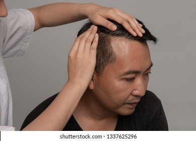 Dermatologist checking patient's hair on grey background. Asian man gray-hair worry hair loss problem for health care shampoo concept.
