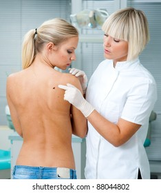 dermatologist doctor inspecting woman patients skin on her back for melanoma