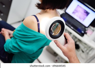 The dermatologist examines the patient's moles with the help of a special electoral magnifying glass. Prevention of melanoma.