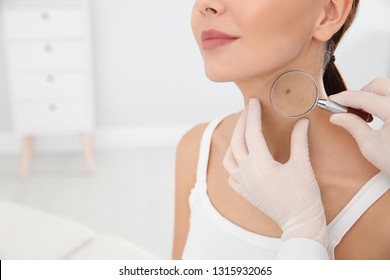 Dermatologist examining patient's birthmark with magnifying glass in clinic, closeup. Space for text