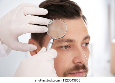 Dermatologist examining patient's birthmark with magnifying glass in clinic