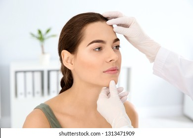 Dermatologist examining patient's face in clinic. Skin cancer checkup