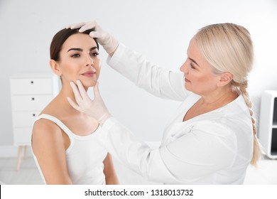 Dermatologist examining young patient's birthmark in clinic