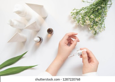 Dermatologist testing organic natural skincare products (serum, essential oil, cream, lotion) for safety and efficacy on white desk. Cosmetic beauty product laboratory testing concept. Top view.