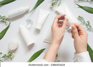 Dermatologist testing organic natural skincare products (serum, essential oil, cream, lotion) for safety and efficacy on white desk. Cosmetic beauty product laboratory testing concept. Copy space.
