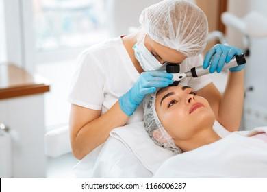 Dermatology clinic. Skilled female dermatologist using a professional dermatoscope while doing the skin examination