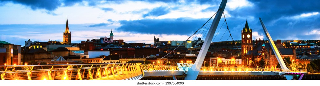 Derry, Ireland. Illuminated Peace bridge in Derry Londonderry in Northern Ireland with city center at the background. Night cloudy sky, reflection in the river.