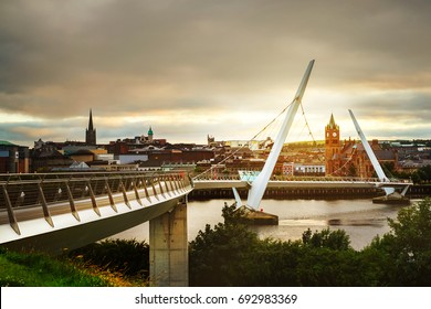 Derry, Ireland. Peace bridge in Derry Londonderry in Northern Ireland with city center at the background. Sunny evening with cloudy sky, reflection in the river