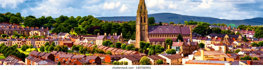 Derry, North Ireland. Aerial view of Derry Londonderry city center in Northern Ireland, UK. Sunny day with cloudy sky, city walls and historical buildings