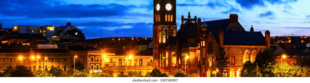 Derry, Northern Ireland. Illuminated Cathedral in Derry Londonderry in Northern Ireland with city center at the background. Night cloudy sky, reflection in the river.