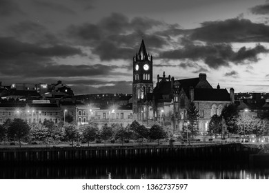 Derry, Northern Ireland. Illuminated Cathedral in Derry Londonderry in Northern Ireland with city center at the background. Night cloudy sky. Black and white
