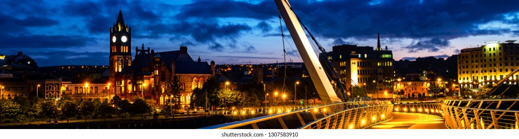 Derry, Northern Ireland. Illuminated Peace bridge in Derry Londonderry in Northern Ireland with city center at the background. Night cloudy sky, reflection in the river.
