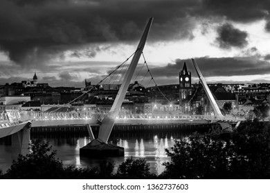 Derry, Northern Ireland. Illuminated Peace bridge in Derry Londonderry in Northern Ireland with city center at the background. Night cloudy sky, reflection in the river. Black and white