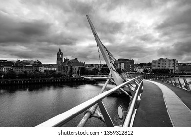 Derry, Northern Ireland. Peace bridge in Derry Londonderry in Northern Ireland, UK with city center at the background. Sunny evening with cloudy sky, reflection in the river. Black and white