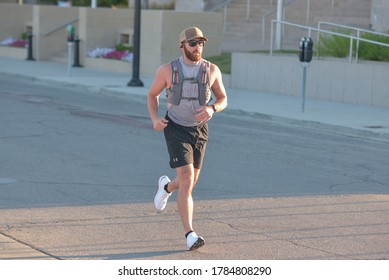 Des Moines, IA / United States of America - July 11th, 2020 : A man runs wearing a hydration backpack down the middle of a street during a socially distanced 5k run / walk, early in the morning.