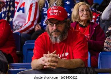 "Des Moines, IA / USA - 01/30/2020: President Donald Trump supporter sporting a red ""Keep America Great"" hat waiting for Trump to speak at his Keep America Great rally in Des Moines, IA"
