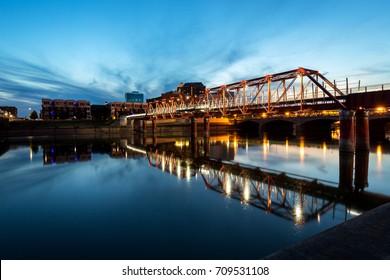 DES MOINES; IOWA - August 12; 2017: Bridges cross a river in downtown Des Moines on a summer evening. Des Moines is the capital city of Iowa.