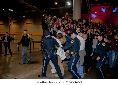 Des Moines Iowa, USA, 8th December, 2016 Des Moines police officers escort out a pair of protesters that were disrupting the Donald Trump victory rally at the Hy-Vee Hall in the event center.