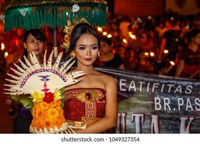 Desa Munggu (Munggu village), Bali, Indonesia. March, 16, 2018. Balinese girl carrying symbol of Dewi Sri on Ngrupuk parade conducted on the eve of Nyepi day.