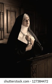 Desaturated image of a young novice nun praying a rosary