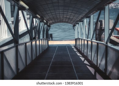 Descending boarding gate covered corridor with plenty of beams, on the quay for passengers of a boat or a ship, with river water in the background, selective focus in a middle, shallow depth of field