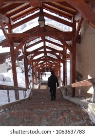 Descending the steps of a covered arcade in small alpine village of Chatel, France