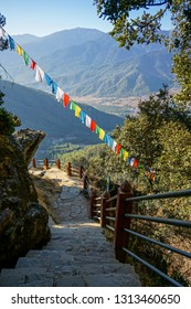 Descending white stone steps and handrail with Buddhist flags strewn across shot at last leg of Teger's nest or Paro Taktsang trail with green Himalayan rolling hills in background on sunny day