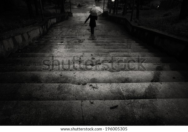 The descent/A person going down the stairs with an umbrella during a heavy rain. Orsova, Romania, May 15, 2010