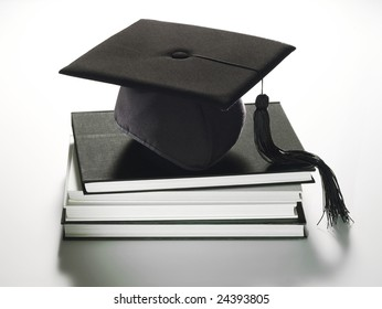 Description: A graduation hat sitting on a stack of books.