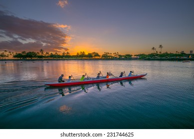Description:  July 7, 2014:   An outrigger canoe team paddles through the Ala Wai Harbor in Honolulu Hawaii at sunset on  July 7, 2014. Title: Hawaiian  Outrigger Canoe