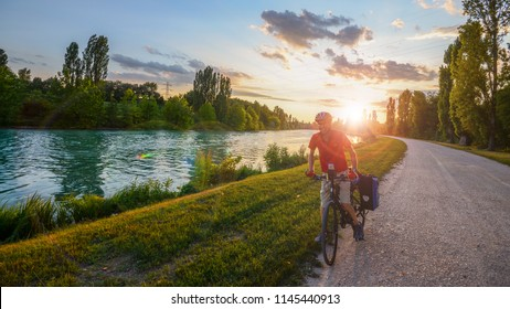 Desenzano del Garda, Italy - July 23, 2018: Man mountain biking on a gravel path along the Mincio River towards Mantova in Veneto, Italy at sunset