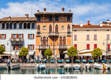 Desenzano del Garda, Italy, on April 27, 2019. The picturesque bay from the beautiful embankment. People eat and have a rest at the tables of cafe. Boats are moored near the embankment.