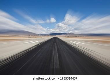 Desert airport runway with dark skid marks and motion blur.