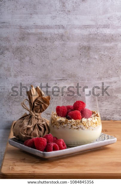 desert, Breakfast, Fresh ripe oatmeal  blackberries, strawberries and raspberries  homemade yogurt in glass on light gray concrete background. Healthy food concept with copy space