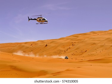 Desert car racing with helicopter