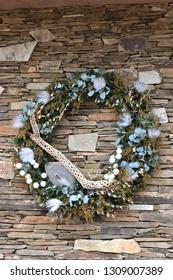 Desert design holiday wreath against a flagstone wall