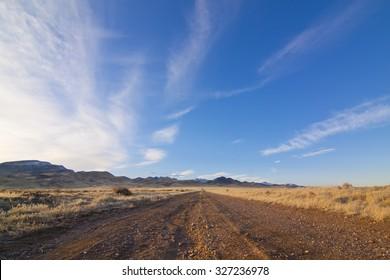 Desert Dirt road with beautiful blue sky.