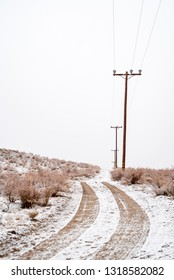 desert dirt road covered in snow with vehicle tire tracks and power poles