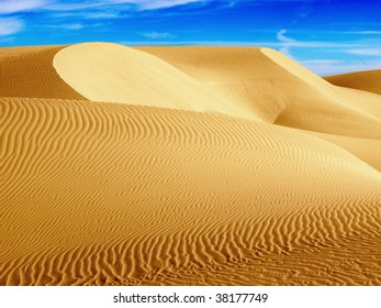 Desert Dunes in Western Egypt. Curves and patterns of sand created by the wind against a vivid blue sky.