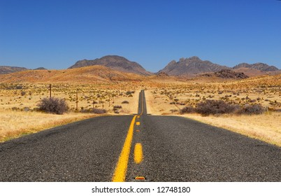 Desert highway into the mountains with yellow stripes