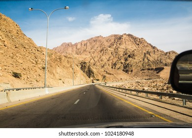 Desert highway and mountains through car window not far from Dead sea in Jordan