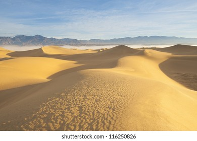 Desert landscape with blue sky and mountain and sand dunes in the foreground