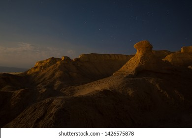 Desert landscape of a yellow orang hills illuminated by the full moon with Mushroom shaped Rock in the model of the frame and blue sky with a lot of stars, Neot HaKikar